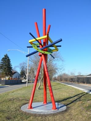 Image of red, yellow, blue, and green metal abstract sculpture in a median