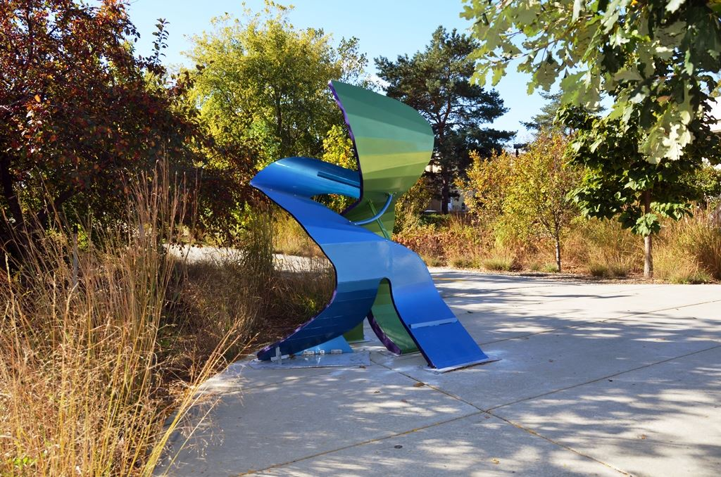 Abstract blue and green metal sculpture on walkway