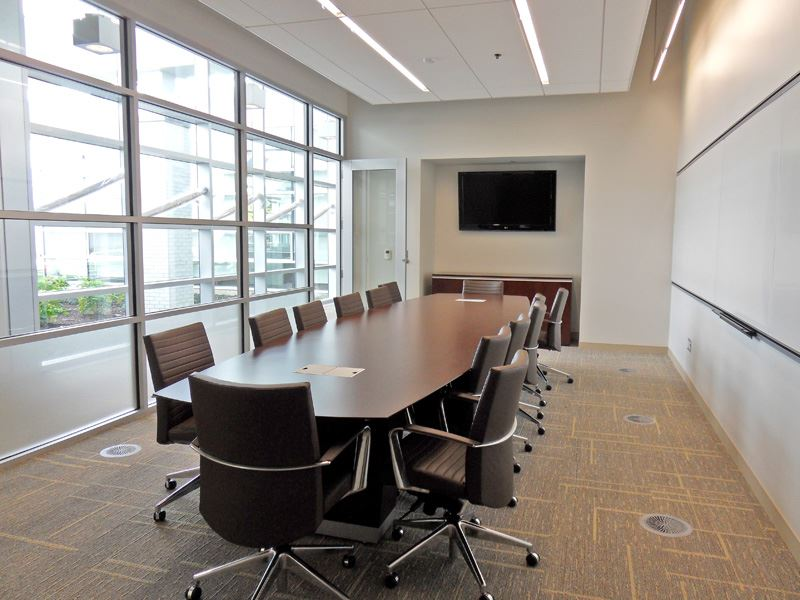 Image of one long conference table with chairs and a television